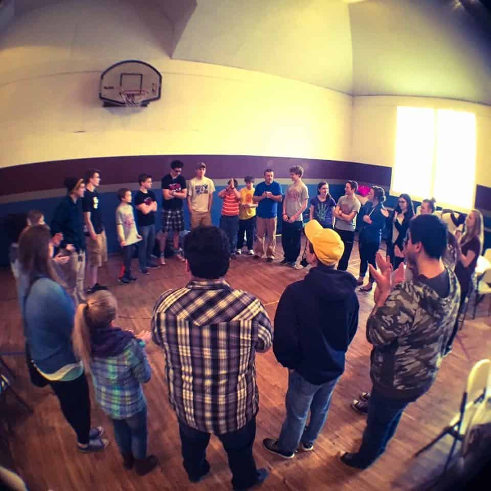 Fisheye view of people standing in a circle in a gymnasium